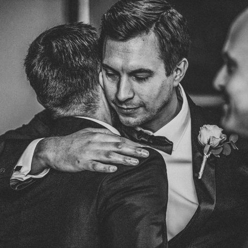 Wedding day hugs with groom and bestman