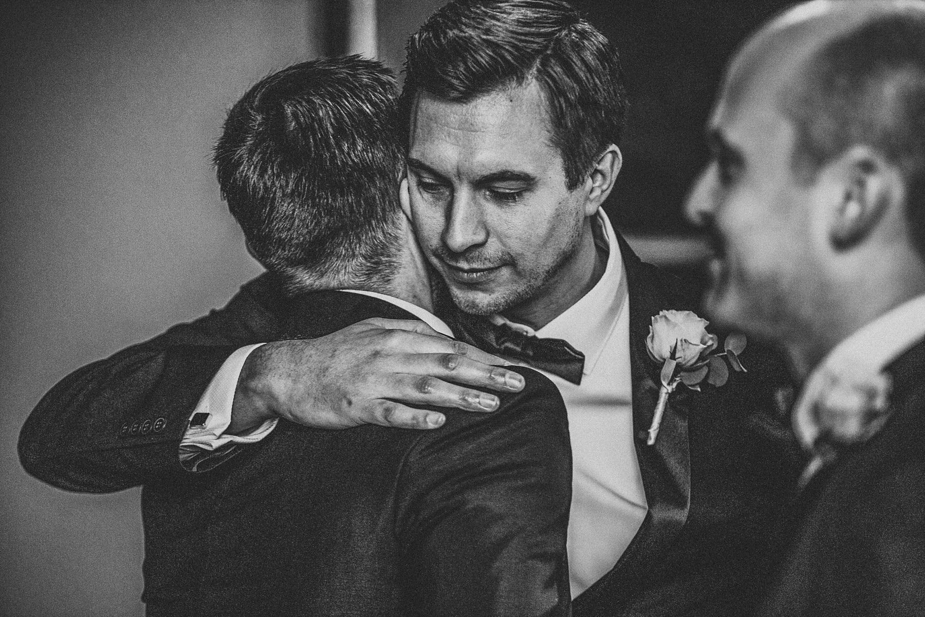 Wedding day hugs with groom and bestman