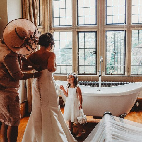 Putting wedding dress on at Coombe Lodge in Bladgon