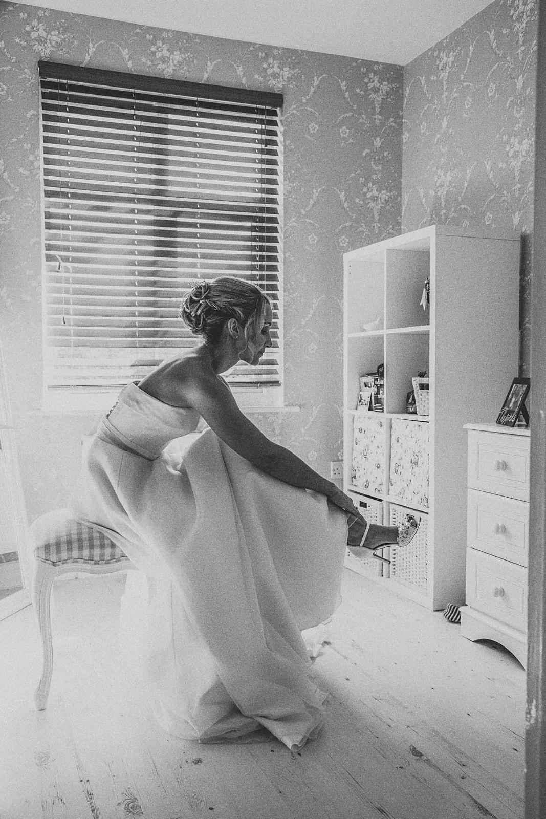 bride putting on wedding shoe